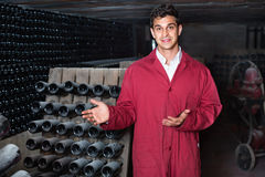 Man winery   working in aging section with bottle racks in cella Stock Photo