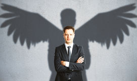Man with winged shadow. Confident businessman with winged shadow on concrete background. Creativity concept Royalty Free Stock Photography