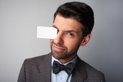 Man winking and holding blank visiting card by Royalty Free Stock Images