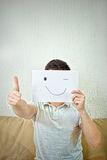Man winking and holding out a raised thumb. Royalty Free Stock Image