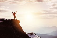 Man in winner pose at mountain top against mountains and sunset. Hiker or traveller stands in winner pose at mountain top against mountains and sunset. Win or Stock Photos