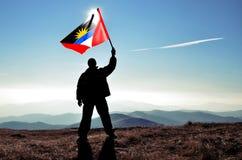 Man winner waving Antigua and Barbuda flag. Successful silhouette men winner waving Antigua and Barbuda flag on top of the mountain peak Stock Photos