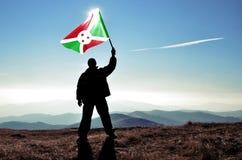 Man winner waving Burundi flag. Successful silhouette men winner waving Burundi flag on top of the mountain peak Stock Photography