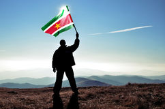 Man winner waving Suriname flag. Successful silhouette man winner waving Suriname flag on top of the mountain peak Stock Photos