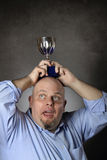 Man with winning trophy over his head Royalty Free Stock Photography