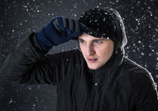 Man with winter cloth looking away with snow Stock Photos