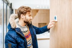 Man adjusting temperature with thermostat at home. Man in winter clothes feeling cold adjusting room temperature with electronic thermostat at home stock photo