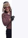 Man in winter clothes and fur hat is pointing to a blank board Royalty Free Stock Images