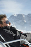 Man In Winter Clothes Relaxing On Chair Against Mountain Stock Images