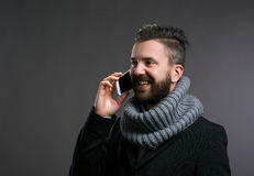 Man in winter clothes with smartphone, making phone call Royalty Free Stock Images