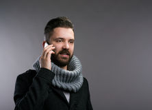 Man in winter clothes with smartphone, making phone call Royalty Free Stock Image
