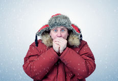 Man in winter clothes warming hands, cold, snow, blizzard.  Royalty Free Stock Photography