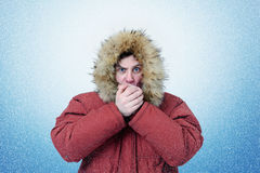 Man in winter clothes warming hands, cold, snow, blizzard Stock Photography