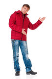 Man in winter clothing. Full length portrait of a young man in winter clothing showing something isolated on white background royalty free stock image