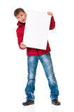 Man in winter clothing. Full length portrait of a young man in winter clothing with empty white board isolated on white background stock photography