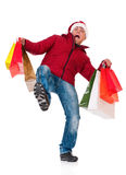 Man in winter clothing. Full length portrait of a young man in winter clothing and Santa hat with shopping bags slipping on floor isolated on white background Stock Photos
