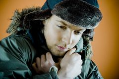 Man In Winter Coat. Portrait of a 21 year old man with a winter coat and hat on, holding the coat closer together at the neck to keep warm.  Taken in horizontal Stock Photos