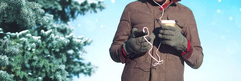 Man in winter day listens to music on a smartphone holds coffee cup. In hand on a christmas tree background Royalty Free Stock Photography