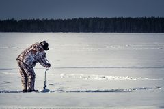 A man on a winter fishing drill hole ice drill stock photography