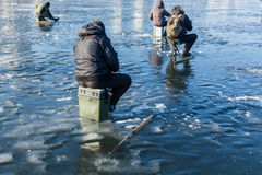 Man on winter fishing, people on the ice of the frozen lake, fis Stock Images