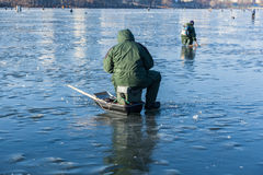 Man on winter fishing, people on the ice of the frozen lake, fis Royalty Free Stock Photo