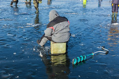 Man on winter fishing, people on the ice of the frozen lake, fis Stock Photos