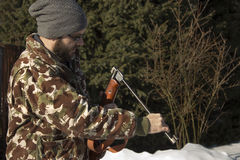 Man in winter forest reloads pneumatic weapons.  Hunter dressed in camouflage with pneumatic gun, rifle. Hunter hunting reload firearms in the winter scenery Stock Photo