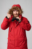 Man in winter jacket holding binoculars and gesturing thumb up Royalty Free Stock Photography