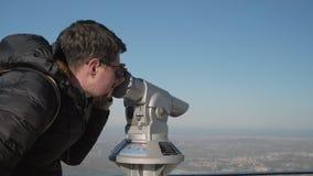 Man looks at cityscape through tourist binoculars. Man in winter jacket looks at cityscape through tourist binoculars on observation deck stock footage