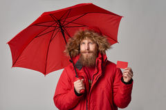 Man in winter jacket with umbrella showing blank credit card. Man in red winter jacket standing under umbrella and showing blank credit card, over grey Stock Photo