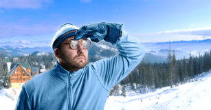 Man in winter mountains. Retro skier in winter mountains looking at view Stock Image