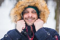 Close up portrait of young man against park covered with snow background stock photo