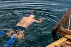 A man - a winter swimmer, swimming in the winter hole royalty free stock image