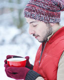 Man in winter warming his hands with hot tea Stock Photo