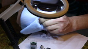 Man wipes a jeweler gold ring after polishing. stock video