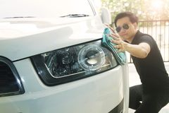 A man is wiping the car with a microfiber cloth. Keep details that focus on the headlights. royalty free stock photo