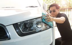 A man is wiping the car with a microfiber cloth. Keep details that focus on the headlights. stock photos