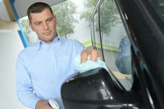 Man wiping car mirror. Man wiping the car mirror Stock Image