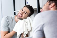 Man wiping face with towel. Happy young man looking at mirror and wiping face with towel Royalty Free Stock Images