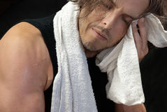 Man Wiping Face After Workout. Close-up of a man wiping of his face after his workout Stock Image
