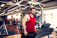 Man with a towel beside a treadmill. Man wiping his face with a towel beside a treadmill royalty free stock photography