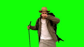 Man wiping his forehead while he is trekking on green screen. In slow motion stock video