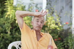 Man wiping his sweat. Old man wiping sweat from his forehead stock images