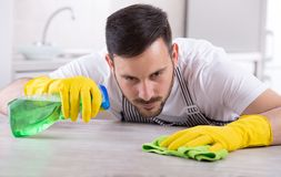 Man wiping kitchen table. Young handsome man with apron and rubber gloves wiping wooden table in kitchen. Cleaning service concept Royalty Free Stock Images