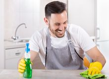 Man wiping kitchen table. Young handsome man with apron and rubber gloves wiping wooden table in kitchen and smiling. Cleaning service concept Stock Photos