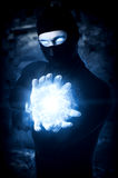 Man witch with Ball from frozen ice. Halloween concept. Powerful Male witch or wizard with blue cold fireball in hands. Ball from frozen ice Stock Images