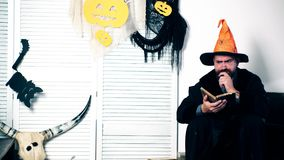 A man in a witch`s suit reads a book and gestures. Halloween party and celebration concept. Family in costumes have fun stock video footage