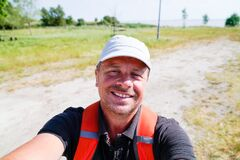 Free Man With A Backpack Hikes Along A Pathway Near River Beach Taking Phone Selfie Photo Stock Images - 187078144