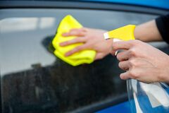Free Man With A Spray Bottle And A Rag In His Hand Wipes The Dirty Glass Of A Car Stock Photography - 175383572