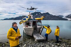 Free Man With Crew Members From Scientific Expedition  Send A Drone Near The Vessel Docked On Iceberg Rock Bay At Wintertime To Explore Stock Image - 197011071